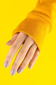 Mão de mulher bonita bem cuidada com design moderno de unhas em amarelo