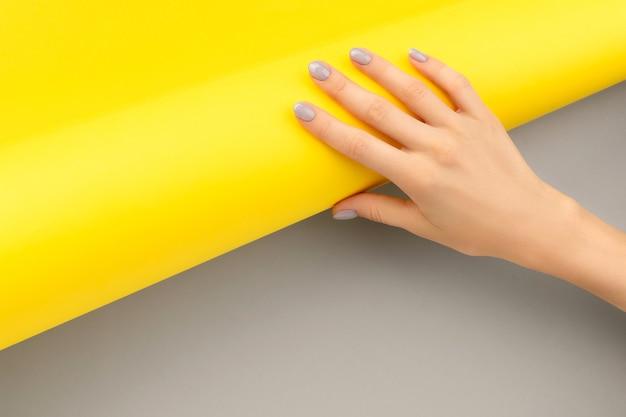 Mão de mulher bonita com design de unhas brilhante em cinza e amarelo