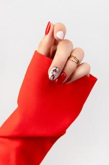 Mão de mulher bonita com manicure vermelha em fundo cinza