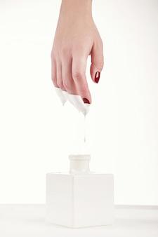 Mão de mulher bonita com manicure vermelha, tinta branca, fundo branco pingando dela. extensão de unha. manicure, salão de spa. criativo, publicidade. relaxar.