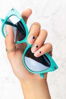 Mão de mulher bonita e bem cuidada com design de unhas nude e azul fosco segurando óculos de sol