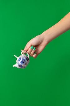 Mão de mulher bonita e bem cuidada com unhas verdes segurando um bule na superfície verde