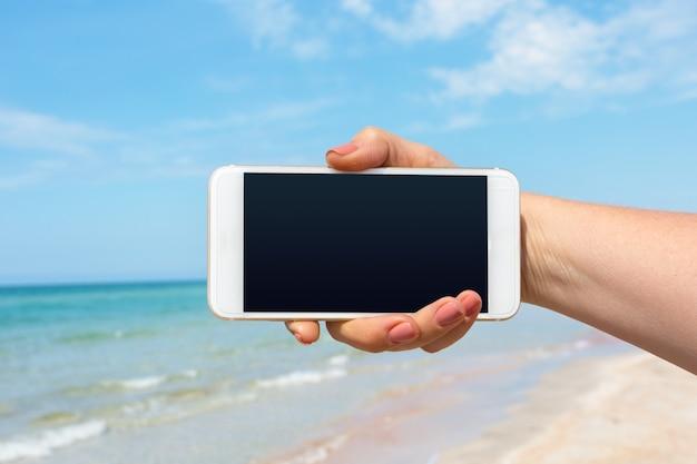 Mão de mulher bonita usando telefone inteligente na praia