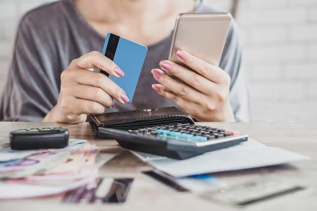 Mão de mulher, calculando a dívida de cartão de crédito com telefone inteligente