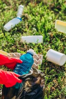 Mão de mulher catando lixo plástico para limpeza no parque.