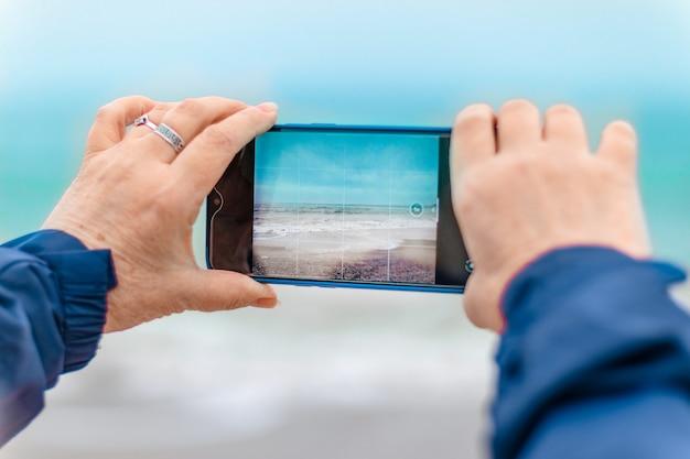 Mão de mulher caucasiana de turista tirando uma foto do mar por telefone na praia, conceito de férias de viagem