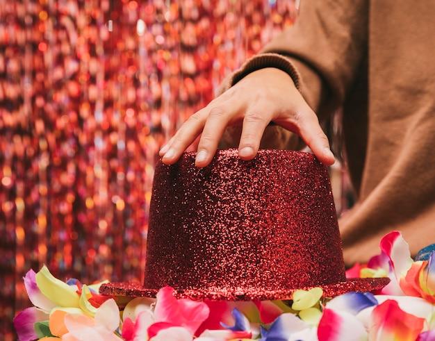 Mão de mulher close-up no chapéu vermelho