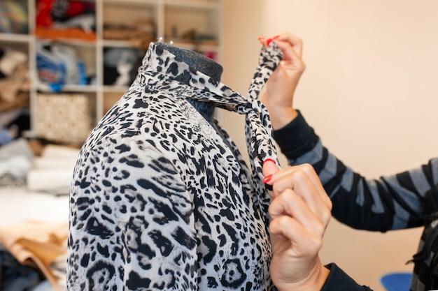 Mão de mulher closeup alisa o vestido com um ferro a vapor em um manequim