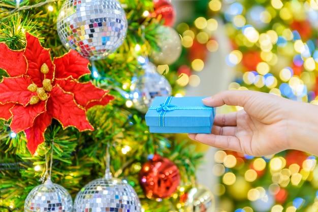 Mão de mulher closeup decorando a árvore de natal em bokeh de fundo