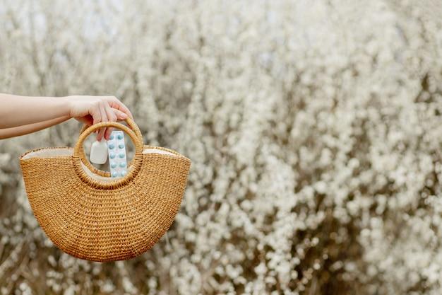Mão de mulher coloca comprimidos de alergia na bolsa no fundo florescendo
