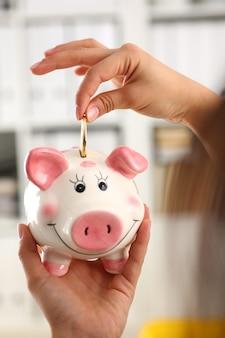 Mão de mulher coloca moeda no sorriso engraçado piggybank