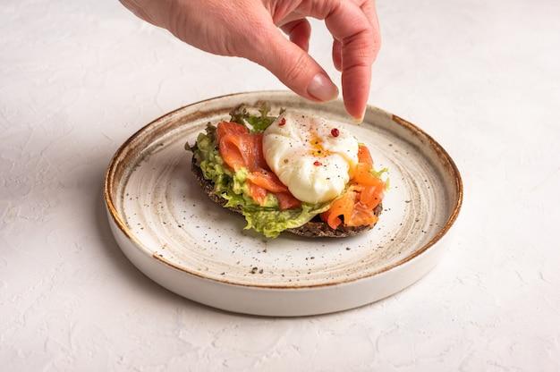 Mão de mulher coloca pimenta na torrada de ovo escalfado com abacate, salmão salgado, rúcula e pão de centeio em um prato de cerâmica, close-up. conceito de comida saudável