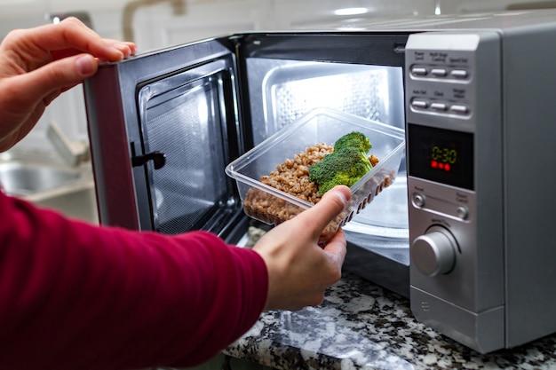 Mão de mulher coloca recipiente plástico com brócolis e trigo sarraceno no microondas