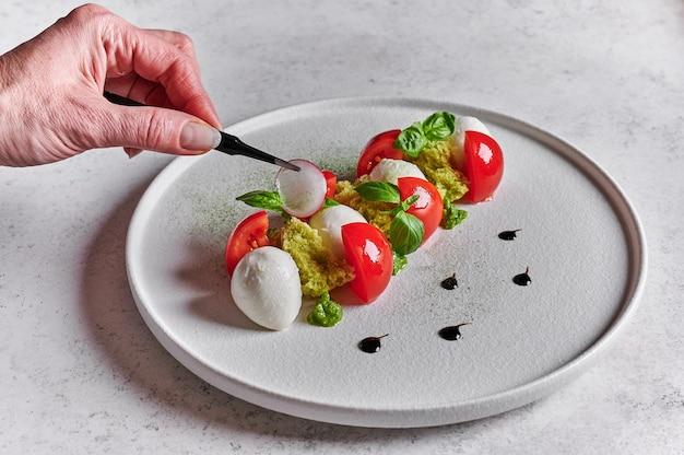 Mão de mulher coloca uma pinça na fatia de rabanete para a deliciosa salada italiana caprese com tomates maduros, manjericão fresco e queijo mussarela