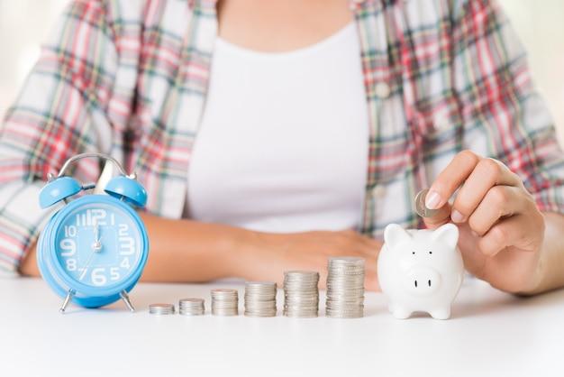 Mão de mulher colocando dinheiro moeda no cofrinho e pilha de moedas e despertador
