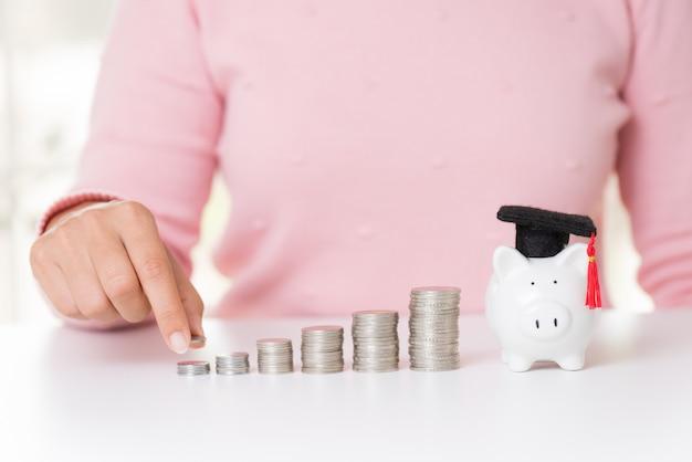 Mão de mulher colocando moedas de dinheiro na pilha de moedas e cofrinho com chapéu de formatura