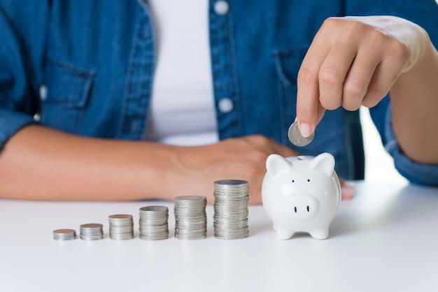 Mão de mulher colocando moedas de dinheiro no cofrinho com pilha de moedas