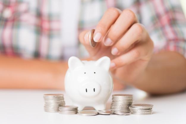 Mão de mulher colocando moedas de dinheiro no cofrinho e pilha de moedas