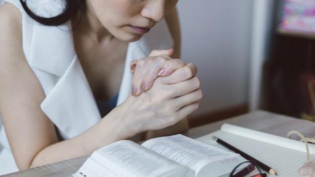 Mão de mulher com a bíblia rezando no cristão