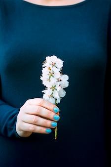 Mão de mulher com as unhas pintadas de azul claro com um suéter azul escuro, segurando delicadamente um galho de amendoeira