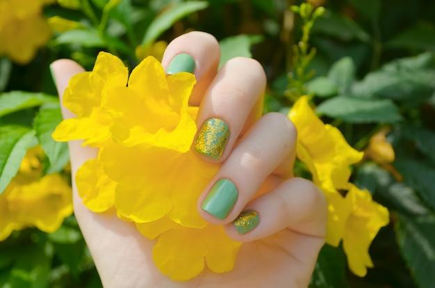 Mão de mulher com brilho verde manicure