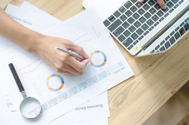 Mão de mulher com caneta e relatório de negócios