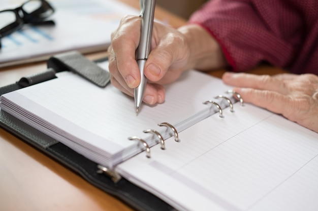Mão de mulher com caneta escrevendo nota no caderno no escritório