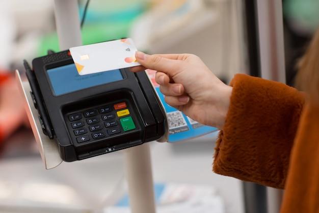 Mão de mulher com cartão de crédito paga compras no caixa da loja pagamento sem contato em novas compras normais