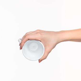 Mão de mulher com copo branco perfeito em branco