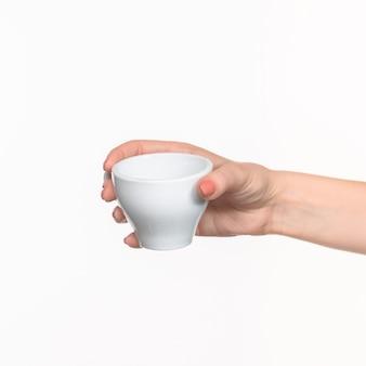 Mão de mulher com copo branco perfeito em fundo branco