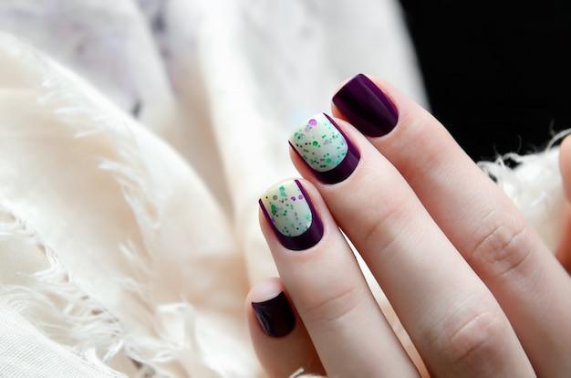 Mão de mulher com design de unha escuro.