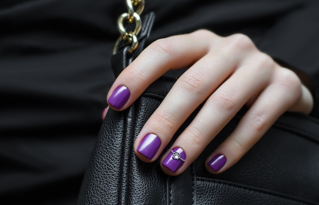 Mão de mulher com design de unhas roxas.