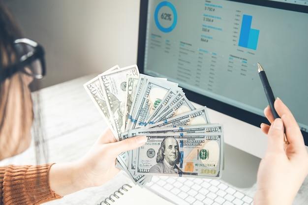 Mão de mulher com dinheiro com gráfico na tela do computador
