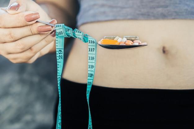 Mão de mulher com excesso de peso segurando a colher com pílulas dietéticas