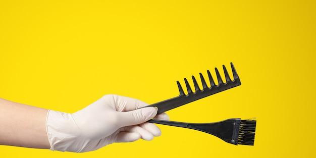 Mão de mulher com ferramentas de um armário de cabelo e acessórios isolados em amarelo