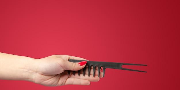Mão de mulher com ferramentas de um cabeleireiro e acessórios isolados