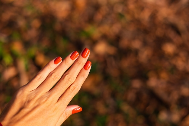 Mão de mulher com manicure laranja