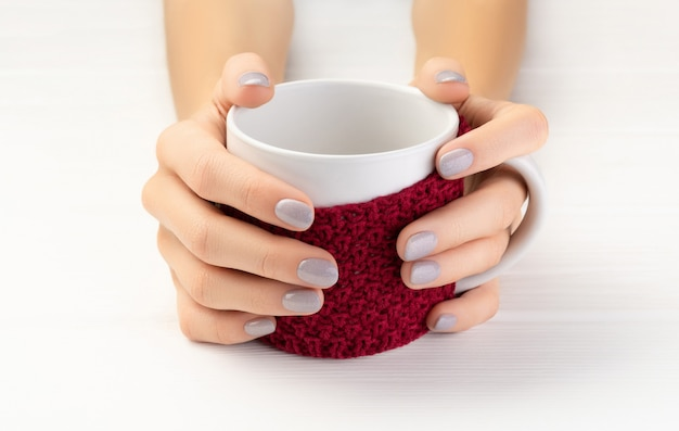 Mão de mulher com manicure segurando copo com bebida quente