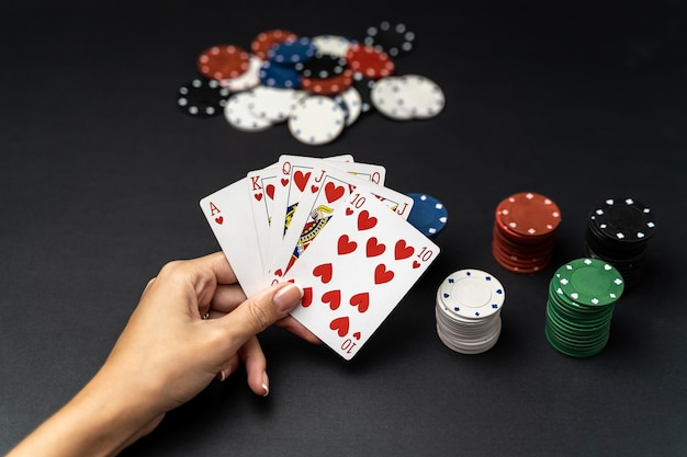 Mão de mulher com mão de royal flush jogando cartas com fichas de poker. conceito de jogo de poker