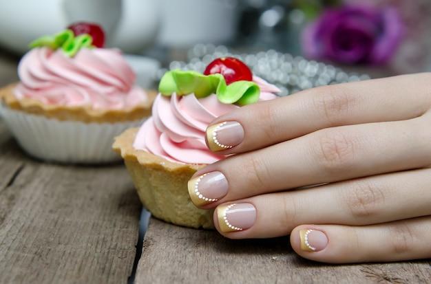 Mão de mulher com ouro francês manicure.