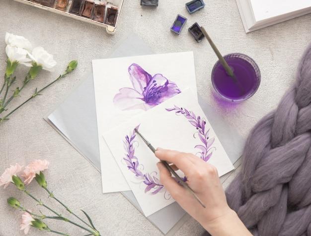 Mão de mulher com pincel desenhando flores roxas. processo de criação de pintura em aquarela