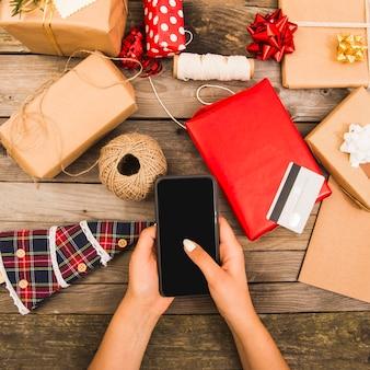 Mão de mulher com smartphone perto de cartão de plástico e conjunto de decorações