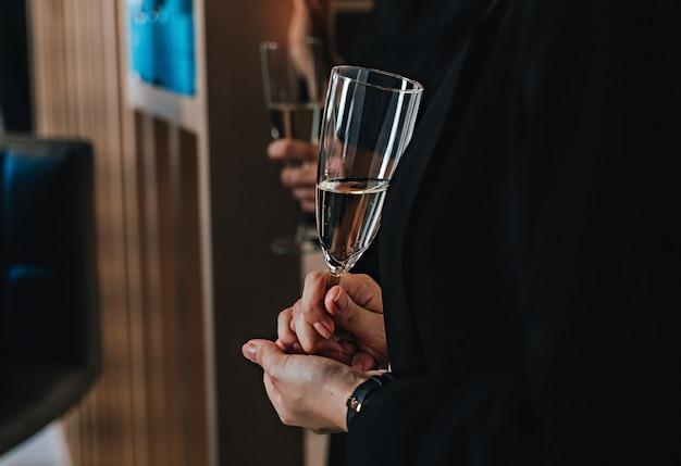 Mão de mulher com taças de champanhe