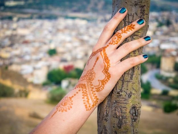 Mão de mulher com tatuagem de henna segurando uma árvore com a bela paisagem urbana