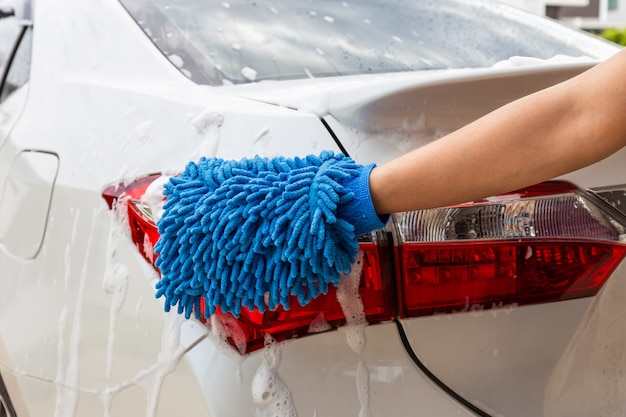 Mão de mulher com tecido de microfibra azul lavar carro moderno luz traseira ou automóvel de limpeza.