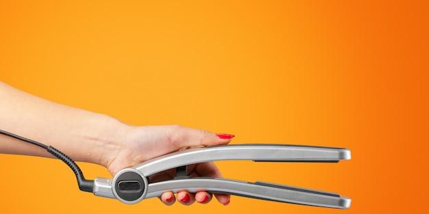 Mão de mulher com um ferro de cabelo isolado em laranja