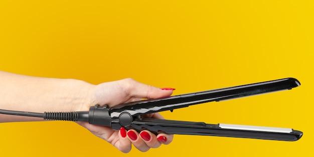 Mão de mulher com um ferro de cabelo isolado em um fundo de cor
