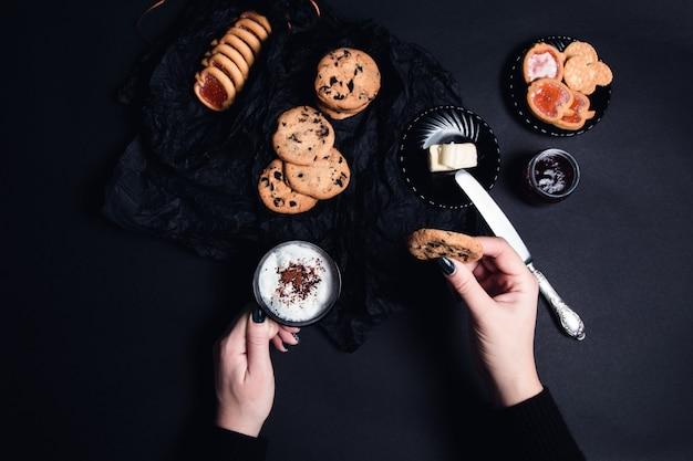 Mão de mulher com uma xícara de café ou cappuccino e chocolate cookies, biscoitos