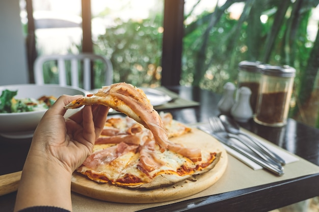 Mão de mulher comer com pizza