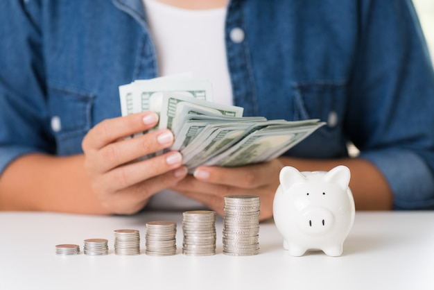 Mão de mulher contando dinheiro de notas de dólares de américa com pilha de moedas e cofrinho